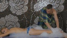 Красивый человек массажируя девушку с пеной в ванне видеоматериал