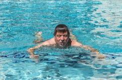 Красивый человек наслаждается поплавать в бассейне Стоковое фото RF