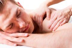 Красивый человек наслаждаясь глубоким массажем задней части ткани Стоковые Изображения