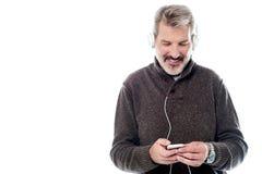 Красивый человек наслаждаясь музыкой на его черни Стоковые Фото