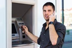 Красивый человек на телефоне на ATM стоковые фотографии rf