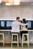 Красивый человек обнимая женщину в баре Стоковые Фото