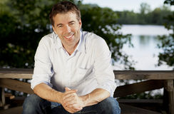 Красивый человек ослабляя на озере стоковое фото
