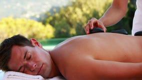 Красивый человек получая горячий каменный poolside массажа видеоматериал