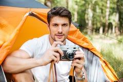 Красивый человек при винтажная камера фото сидя в touristic шатре стоковые изображения