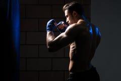 Красивый человек работая бокс сумки в студии стоковые изображения