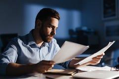 Красивый человек работая самостоятельно на ноче Стоковое Фото