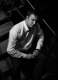 Красивый человек сидя на лестницах Стоковое Изображение