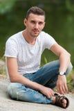 Красивый человек сидя озером Стоковые Фото