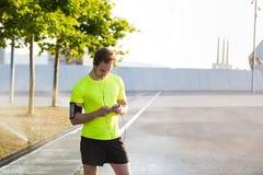 Красивый человек спорт используя его мобильный телефон пока слушающ к музыке и имеющ остатки во время утра jog в городском парке Стоковое Изображение RF