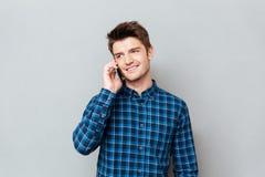 Красивый человек стоя над серой стеной и говоря телефоном стоковая фотография
