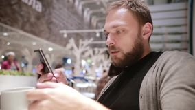 Красивый человек с бородой радостно сидит в кафе, выпивает кофе или чай, использует его smartphone, кивает самомоднейшая технолог сток-видео