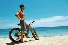 Красивый человек с велосипедом Солнцем загорая на пляже каникула территории лета katya krasnodar стоковые изображения