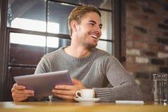 Красивый человек усмехаясь и держа планшет стоковое изображение
