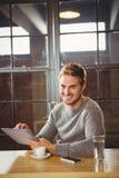 Красивый человек усмехаясь и используя планшет стоковое фото