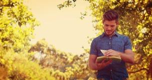 Красивый человек читая книгу в парке сток-видео