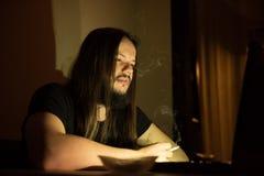 Красивый человек smocking сигареты перед его компьютером Стоковое Фото