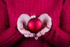 Красивый шарик рождества в женских руках на предпосылке красного kn Стоковые Изображения RF