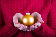 Красивый шарик рождества в женских руках на предпосылке красного kn Стоковое Изображение RF