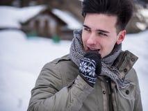 Красивый шоколад молодого человека сдерживая в снеге стоковые изображения rf