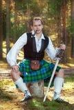 Красивый шотландский человек с шпагой и трубой Стоковая Фотография
