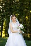 Красивый bridal букет в руках молодой невесты одел в белом платье свадьбы Стоковое Фото