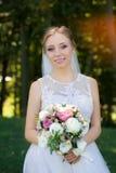Красивый bridal букет в руках молодой невесты одел в белом платье свадьбы Стоковые Фотографии RF