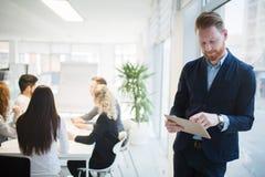 Красивый CEO (главный исполнительный директор) бизнесмена работая в офисе Стоковое Изображение RF