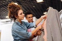 Красивый dressmaker добросердечно смотря одежды пока работающ стоковое изображение