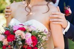 Красивый groom в синем костюме нежно держа красивую невесту с bridal букетом роз и пионов  стоковые фото