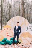 Красивый groom представляя в часах леса осени декоративных на предпосылке Стоковые Изображения RF