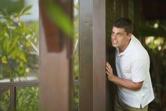 Красивый peeking молодого человека, ища что-то близко к windo Стоковые Изображения RF