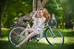 Красивый redhead ослабляя с велосипедом в парке лета Стоковое Фото
