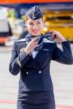 Красивый stewardess одетый в официальной темно-синей форме авиакомпаний Аэрофлота на авиаполе Воздушные судн пассажирского самоле стоковое изображение