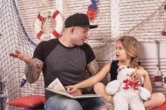 Красивый tattoed человек тратит время с его маленькой милой дочерью Чтение сказок пока дочь сидит рядом стоковые фото