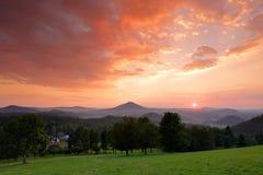 Красивый twilight ландшафт захода солнца Вечер в холмах с деревнями Солнце с Пингом и небом апельсина Солнце вечера во время захо стоковое изображение
