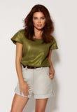Красивыми девушка загоренная детенышами с темным вьющиеся волосы, мягкий состав одела в сияющей зеленой рубашке, бежевых шортах с Стоковое Изображение