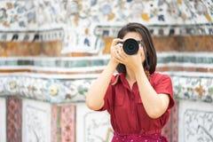 Красивым камера женщины держат туристом, который для того чтобы захватить памяти Висок Wat Arun в Таиланде использование как конц стоковые фото