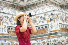 Красивым камера женщины держат туристом, который для того чтобы захватить памяти Висок Wat Arun в Таиланде использование как конц стоковые фотографии rf
