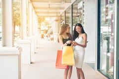 2 красивых азиатских женских друз стоя и смотря в бумаге Стоковое Изображение RF