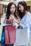 2 красивых азиатских shopaholic женщины с smartphone и colorfu Стоковые Изображения RF