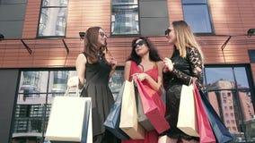 3 красивых дамы обсуждая их день покупок outdoors движение медленное акции видеоматериалы