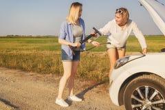 2 красивых белокурых девушки ремонтируют автомобиль на проселочной дороге в лучах Стоковые Изображения