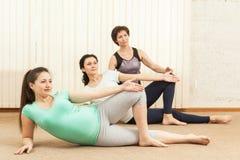 2 красивых беременной женщины делая йогу с тренером Стоковые Изображения RF