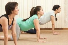 2 красивых беременной женщины делая йогу с тренером Стоковое фото RF