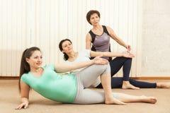 2 красивых беременной женщины делая йогу с тренером Стоковое Фото