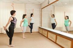 2 красивых беременной женщины делая йогу с тренером Стоковая Фотография