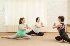 2 красивых беременной женщины делая йогу с тренером Стоковые Фото