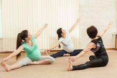 2 красивых беременной женщины делая йогу с тренером Стоковое Изображение RF