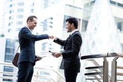2 красивых бизнесмена говорят и дающ рему кулака на городе стоковые изображения